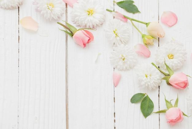 Flores cor de rosa e brancas em fundo branco de madeira