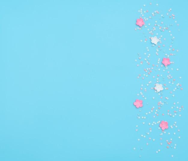 Flores cor de rosa e brancas feitas de foamiran com confetes em forma de estrela sobre fundo azul.