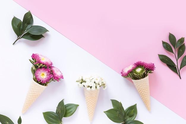 Flores cor-de-rosa e brancas no cone de gelado do waffle na superfície dupla