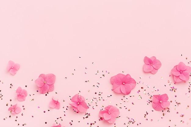 Flores cor de rosa e glitter em um fundo rosa