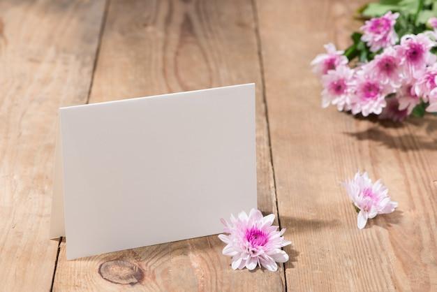 Flores cor de rosa e papel vazio para o seu texto em fundo de madeira