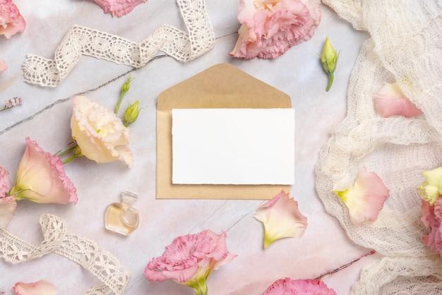 Flores cor de rosa e um cartão em branco com envelope deitado sobre uma mesa de mármore decorada com fitas vintage, pétalas e frasco de perfume. cena de simulação. postura plana feminina