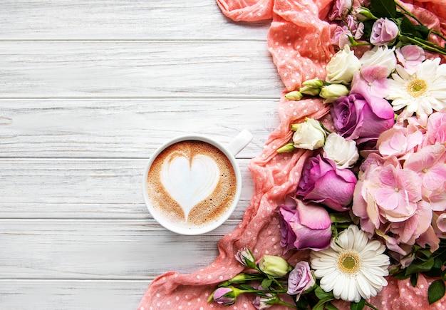 Flores cor de rosa e uma xícara de café em um fundo branco de madeira