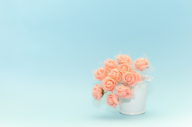 Flores cor de rosa em um balde de brinquedo branco sobre um fundo azul claro, flores para o feriado