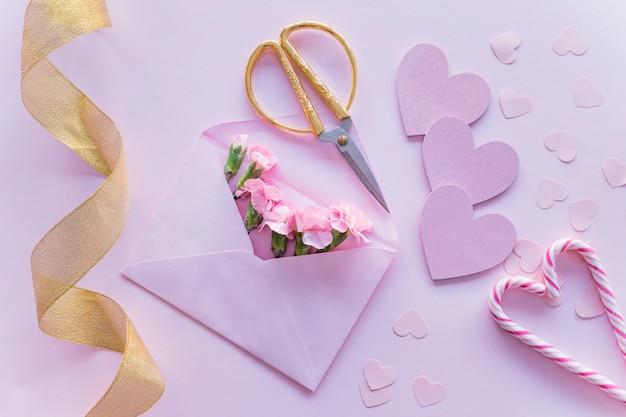Flores cor de rosa no envelope com corações de papel