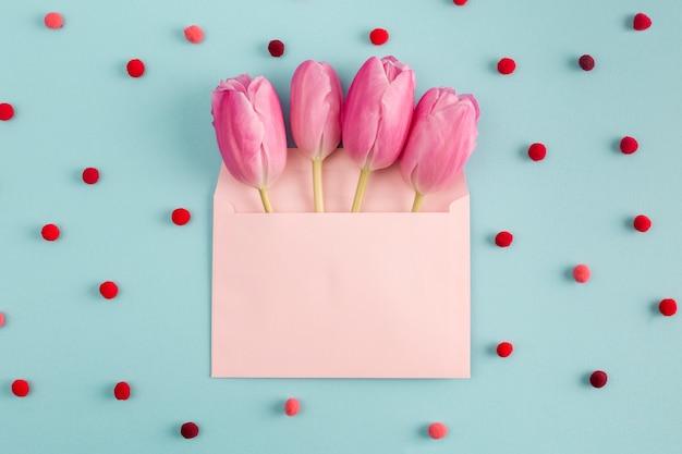 Flores cor de rosa no envelope entre confete macio