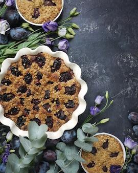 Flores da primavera, ameixas e torta de creme em uma tigela