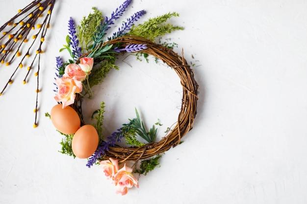 Flores da primavera brilhante, grinalda com ovos de páscoa em cinza