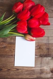 Flores da primavera. buquê de tulipas vermelhas com cartão na mesa de madeira marrom. dia das mães e dia dos namorados conceito. configuração plana