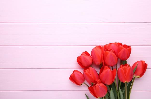 Flores da primavera. buquê de tulipas vermelhas em fundo rosa.