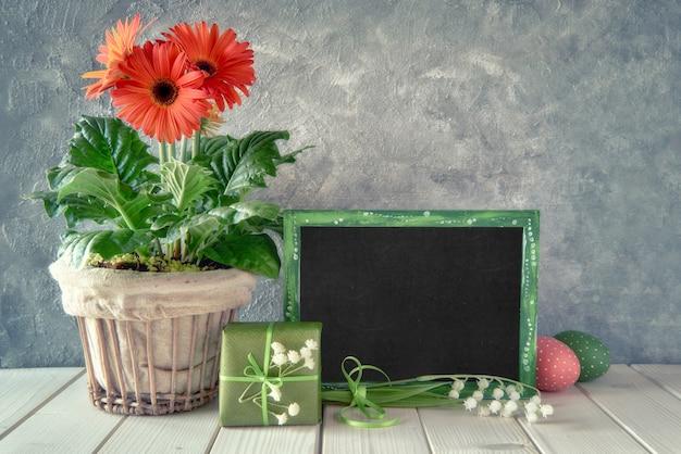 Flores da primavera, decorações de páscoa e um quadro negro na mesa branca, saudações em um quadro negro