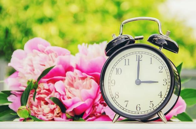 Flores da primavera e despertador. mude a hora.
