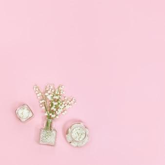 Flores da primavera e linda garrafa de vidro com pétalas secas para aromaterapia