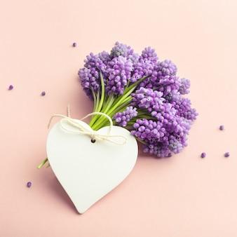 Flores da primavera e um cartão vazio em forma de coração no fundo rosa