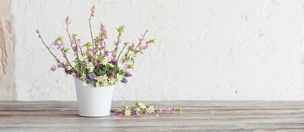 Flores da primavera em balde branco na parede branca velha