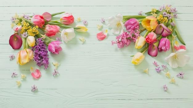 Flores da primavera em fundo verde de madeira