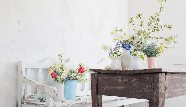 Flores da primavera em interior branco vintage com banco de madeira velho