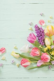 Flores da primavera em superfície verde de madeira