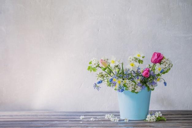 Flores da primavera em um balde azul na superfície branca