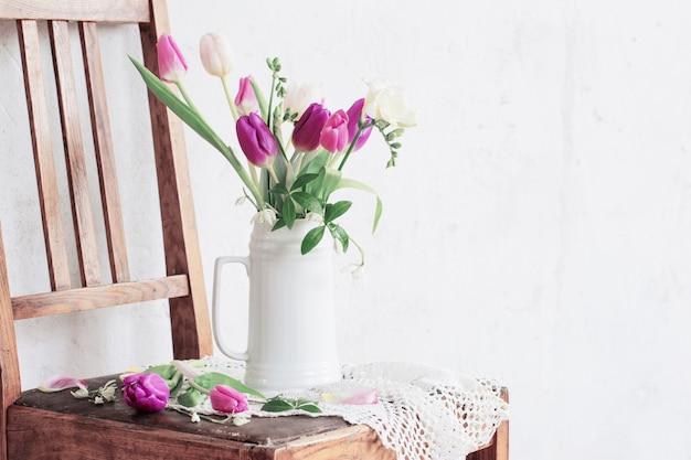 Flores da primavera em uma cadeira velha na velha parede branca de fundo