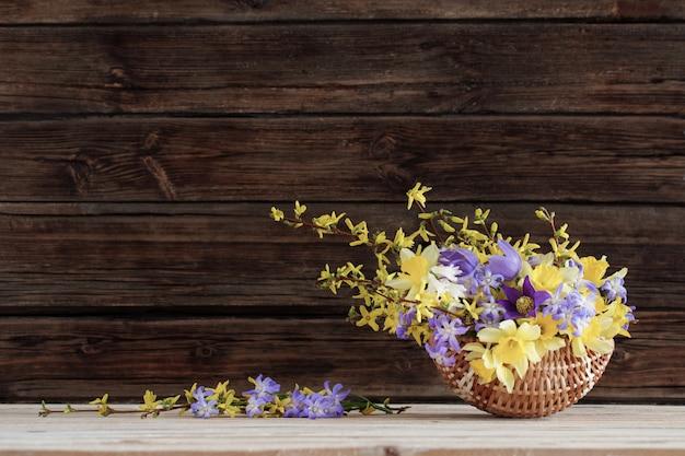 Flores da primavera em uma cesta em uma superfície de madeira escura