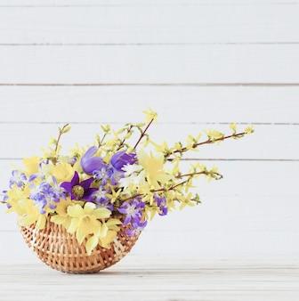 Flores da primavera em uma cesta na superfície de madeira branca