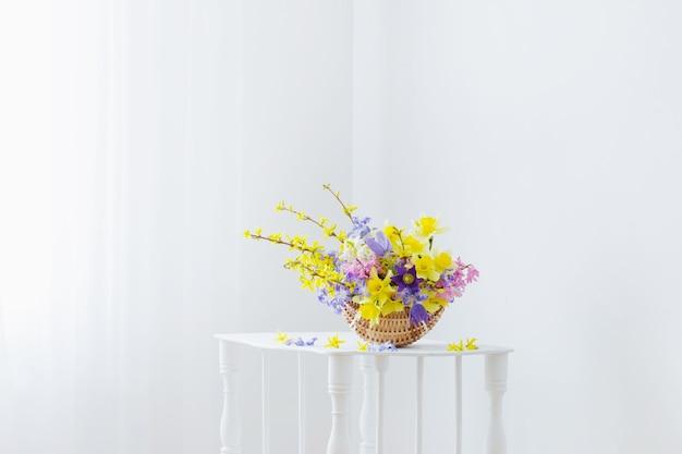 Flores da primavera em uma cesta no interior branco