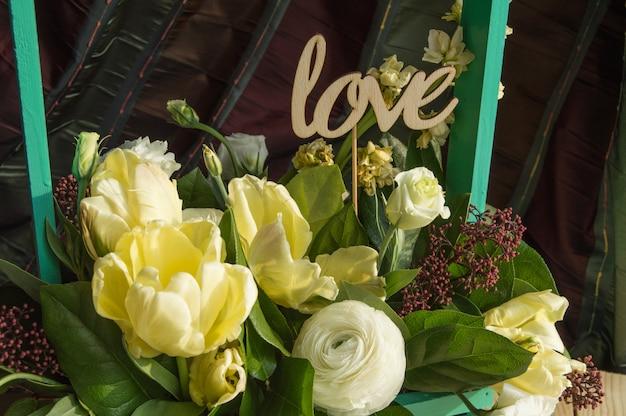 Flores da primavera na caixa de madeira e topper amor, dia dos namorados, casamento