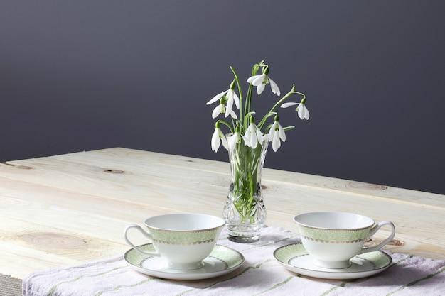 Flores da primavera snowdrops, duas xícaras na mesa de madeira