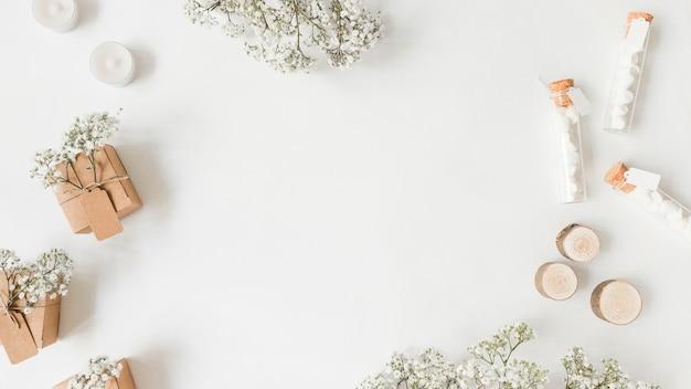 Flores da respiração do bebê; caixas de presente; velas e tubo de ensaio com marshmallow no pano de fundo branco