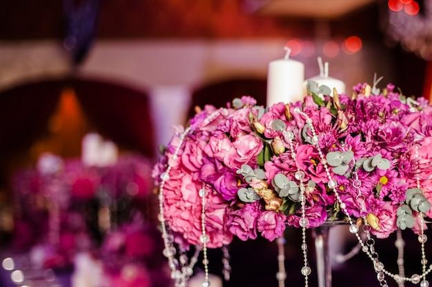 Flores da tabela do banquete de casamento e velas brancas na tabela.