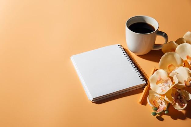 Flores da xícara de café e um caderno no fundo