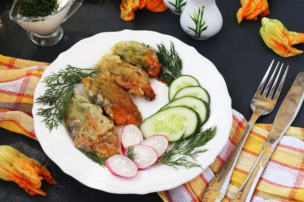 Flores de abobrinha, cozidas na massa, rodelas de pepino e rabanete em um prato
