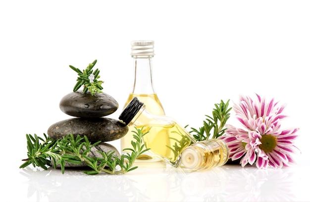 Flores de alecrim frescas, folhas verdes e óleo no frasco isolado no branco.