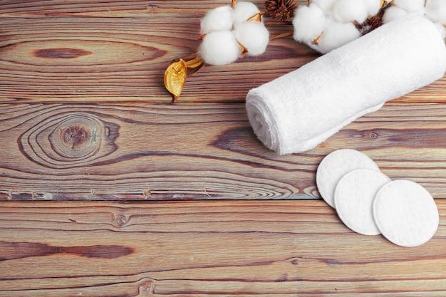 Flores de algodão com toalha na mesa de madeira