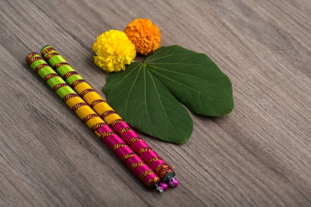 Flores de calêndula festival indiano dussehra e navratriand com varas dandiya em um fundo de madeira