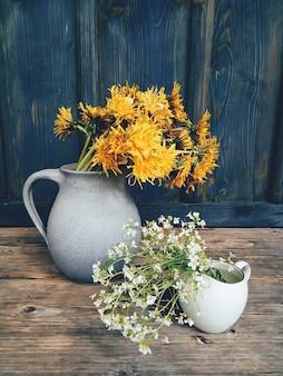 Flores de campo amarelo lindo em copos de mesa de madeira