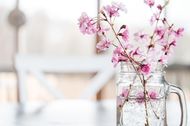 Flores de cerejeira e galhos em um copo d'água em cima da mesa sob as luzes