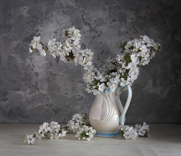Flores de cerejeira em um vaso branco sobre fundo cinza.