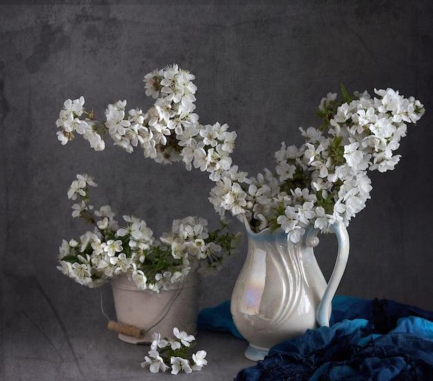 Flores de cerejeira em vaso branco em cinza