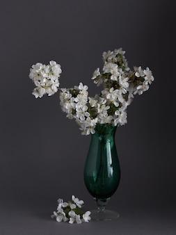 Flores de cerejeira em vaso glasse em fundo cinza. primavera ainda vida.
