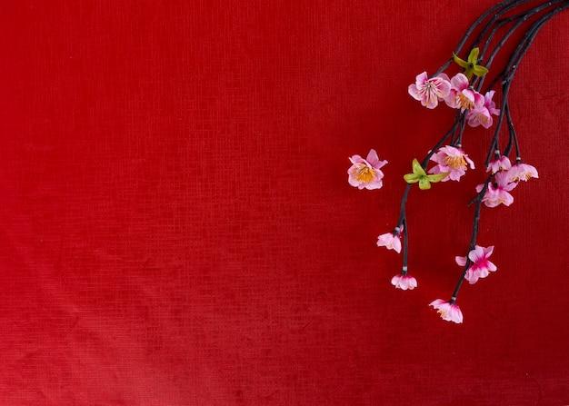 Flores de cerejeira no fundo de papel vermelho, primavera