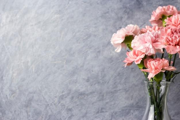 Flores de cravo-de-rosa em garrafa transparente com espaço de cópia
