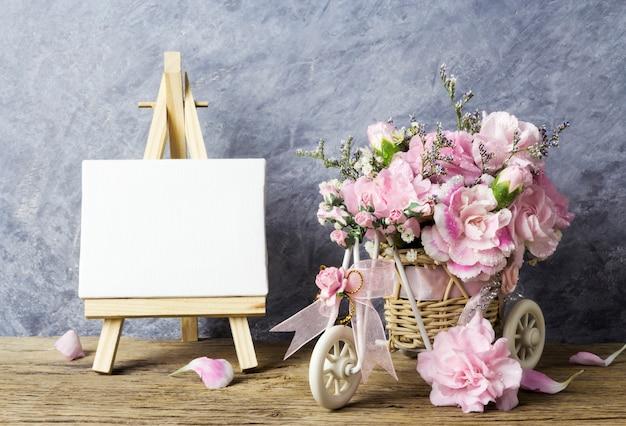 Flores de cravo-de-rosa na cesta de bicicleta e quadro de tela em branco em cavalete