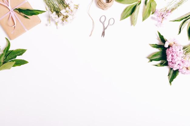 Flores de cravos, presentes, fitas e papel de embalagem em uma mesa branca