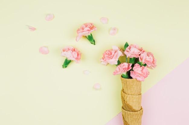 Flores de cravos rosa nos cones de waffle no pano de fundo duplo rosa e amarelo
