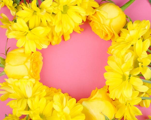 Flores de crisântemo amarelo brilhante e rosas formando um fundo de quadro de círculo