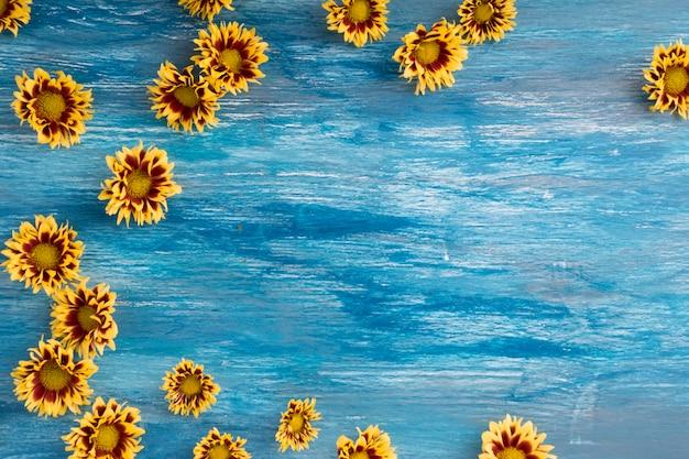 Flores de crisântemo amarelo no cenário texturizado de madeira