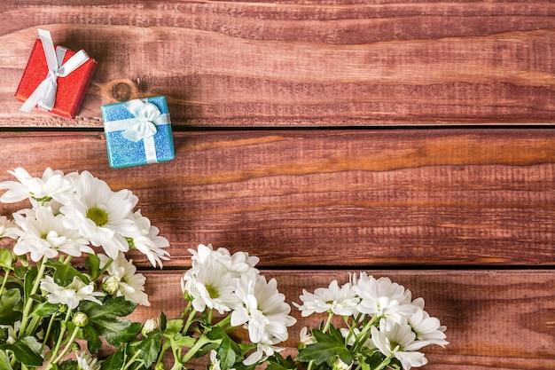 Flores de crisântemo branco com caixas de presente com fundo de madeira