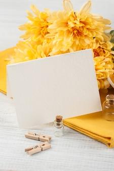 Flores de crisântemo em uma mesa de madeira, papel em branco